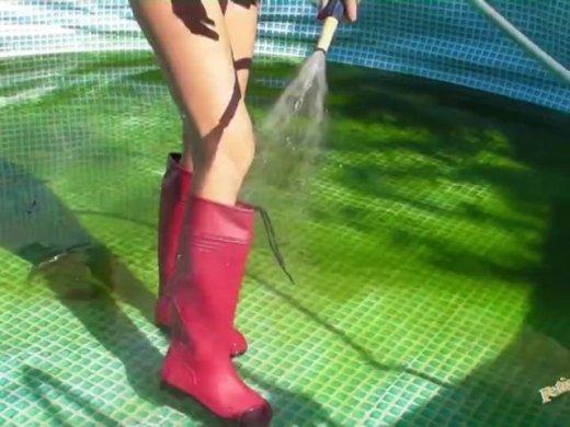 Pool sauber machen in Gummistiefel und Badeanzug
